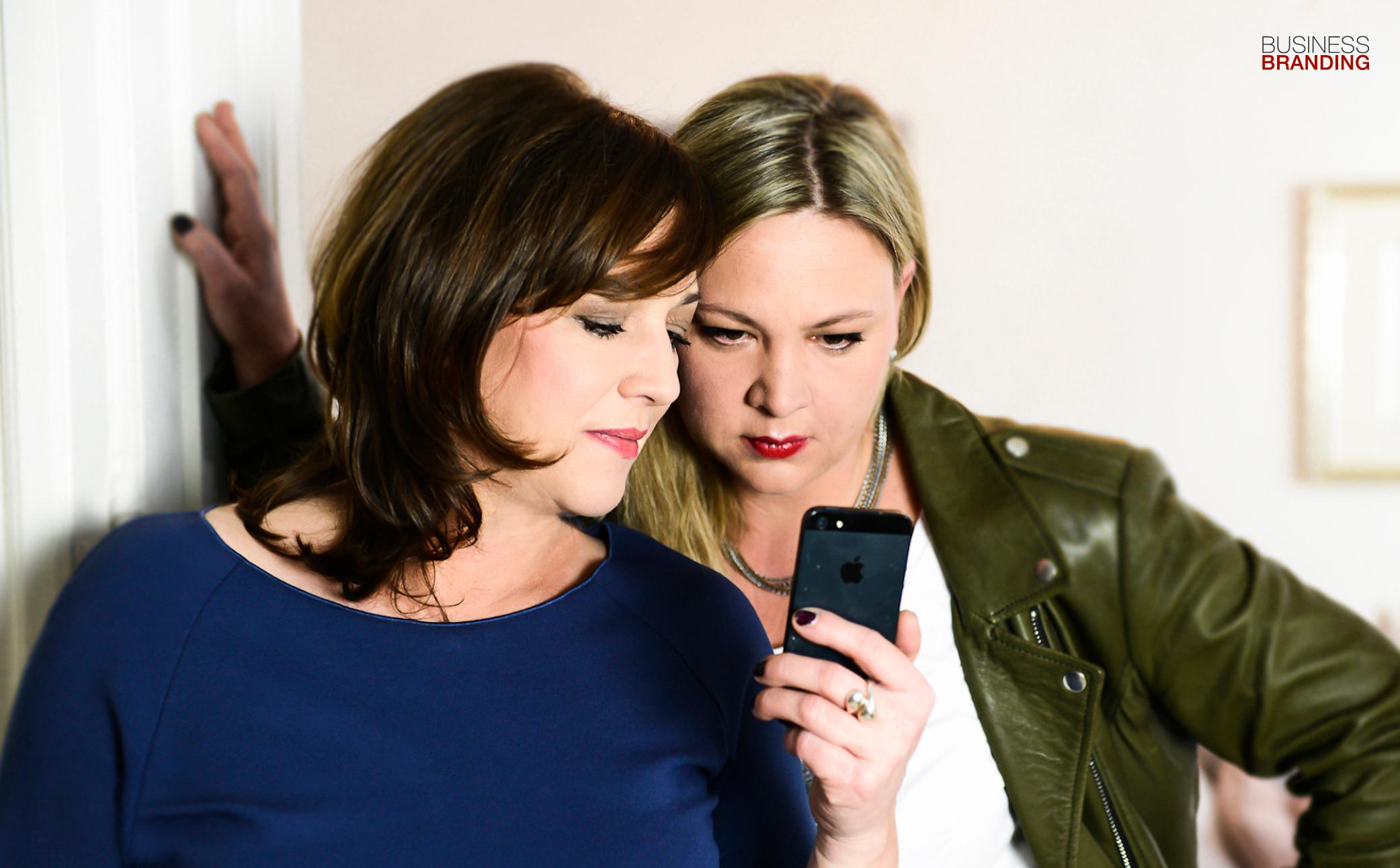 Hier sehen Sie ein Bild mit zwei Frauen die auf ein Handy schauen - Business Portraits - Business Branding Fotograf Berlin